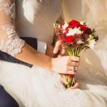 Groom hugging bride holding wedding bouquet — Stock Photo #62829467