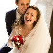 Happy laughing bride and groom on street at sunny day — Stock Photo #62829657