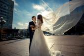 Bride with long veil hugging with groom on street at windy day — Stock Photo