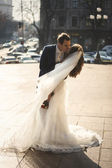 Bride and groom hugging at windy day on city street — Stock Photo