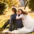 Happy bride hugging groom sitting on yellow leaves at park — Stock Photo #62830423