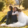 Just married couple relaxing on grass at autumn park — Stock Photo #62830457