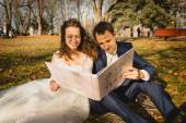 Just married couple sitting on grass at park and watching photos — Stock Photo