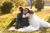 Just married couple relaxing on grass at autumn park — Stock Photo