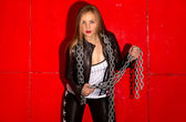 Woman in leather jacket posing with metal chains against red bac — Stock Photo