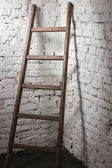 Old wooden ladder leaning against white brick wall — Stock Photo