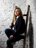 Sexy blonde woman in jacket sitting on wooden ladder at studio — Stock Photo
