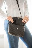 Young stylish woman taking cellphone out of handbag — Stock Photo