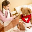 Girl sitting on bed and doing injection to brown teddy bear — Stock Photo #64341243