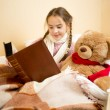 Cute little girl lying in bed and reading book to teddy bear — Stock Photo #64341325