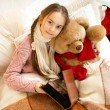Cute girl reading book to teddy bear at bed — Stock Photo #64341355
