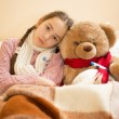 Sad girl with flu lying in bed with teddy bear — Stock Photo #64341401