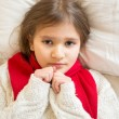 Little sad girl in white sweater lying under blanket at bed — Stock Photo #64342849