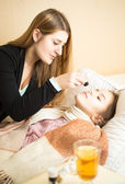 Caring mother spraying daughters nose lying in bed — Stock Photo
