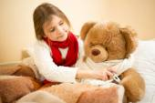 Girl lying in bed and measuring teddy bears temperature with the — Photo