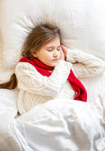 Portrait of little girl in sweater sleeping at bed — Stock Photo