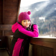 Cute smiling girl posing on balcony against snowy Alps — Stock Photo #64412271