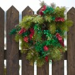 Christmas wreath with red berries hanging on wooden fence — Stok fotoğraf #64412587