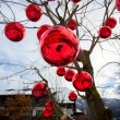 Closeup shot of tree on street decorated with big red balls — Stock Photo #64412651