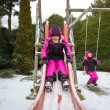 Two little girls having fun on playground at cold snowy day — Stock Photo #64413391
