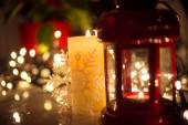 Christmas lights, burning candle and vintage lantern on table — Stock Photo