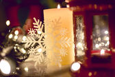 Closeup shot of burning candle on decorated Christmas table — 图库照片
