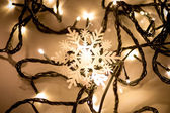 Decorative snow flake lying on christmas lights — Zdjęcie stockowe