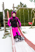 Smiling girl on slide at cold snowy day — Stockfoto