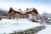 Wooden house in Austrian Alps covered with show — Stock Photo