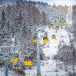 Panoramic shot of long line of cable cars on ski slope — Stock Photo #64644733
