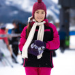 Smiling girl in pink ski suit posing against high mountain cover — Stock Photo #64645167