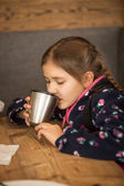 Portrait of cute girl drinking tea from thermos at cafe — Stock Photo