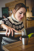 Portrait of woman in sweater pouring coffee from thermos in cup — Stock Photo