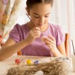 Concentrated girl painting Easter eggs at table — Stock Photo #66161490