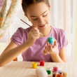Portrait of cute girl with brush painting Easter eggs — Stock Photo #66161526