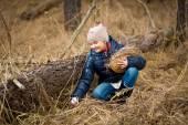 Girl reaching for Easter egg under log in forest — Stock Photo