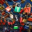 Постер, плакат: Closeup shot of locks symbolizing love hanging on bridge