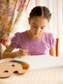 Concentrated girl drawing on canvas by oil paints — Stock Photo