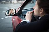 Geschäftsfrau im Auto sitzen und Lippenstift anwenden — Stockfoto