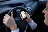 Woman entering number on mobile phone while driving a car — Stock Photo