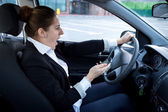Distracted woman using smartphone and driving a car — Stock Photo