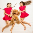 Two sisters lying on floor and playing with teddy bear — Stock Photo #69497063