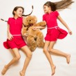 Two smiling girls lying on floor and holding teddy bear — Stock Photo #69497081