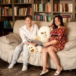 Pregnant woman and smiling husband reading book to teddy bear on — Stock Photo #69613813