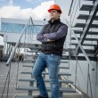Young architect in hard hat posing on metal staircase — Stock Photo #70090033