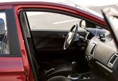 Red car with open passenger seat door — Stock Photo