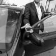 Black and white closeup of car sales manager holding key on hand — Stock Photo #70219431