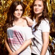 Two sexy brunette girls posing against golden background — Stock Photo #70814525