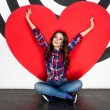 Concept photo of happy woman sitting on floor with big red heart — Stock Photo #70815153