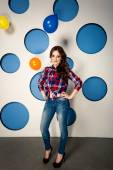 Smiling girl in jeans posing against background with balloons — Stock Photo